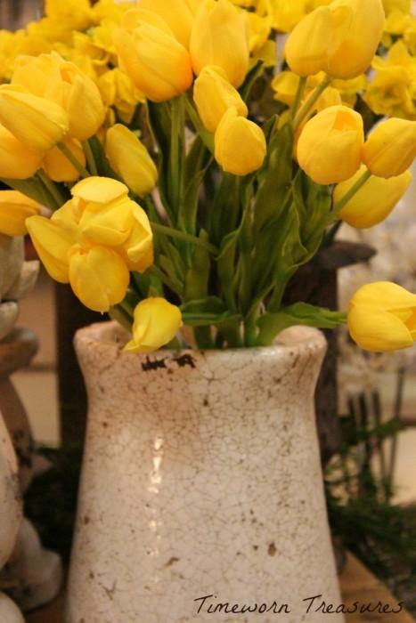 Yellow lifelike tulips in crackled vase